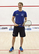 a man holding a a squash racquet on standing on a squash court