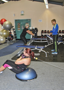 two women exercising in a gym with a personal trainer