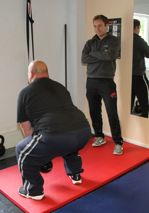 personal trainer supervising a client doing an exercise with a kettle bell weight