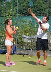 coach demonstrating an action to a young woman